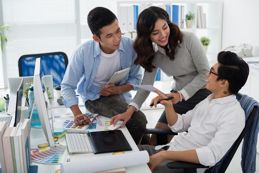 Three colleagues working at a web developer staffing agency