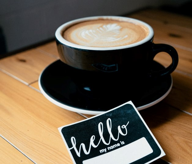 cappuccino in black mug with hello name tag remote onboarding