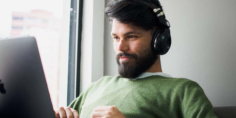 Man On Laptop Listening to Music for Productivity
