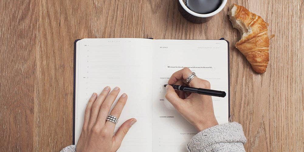 women setting goals in planner