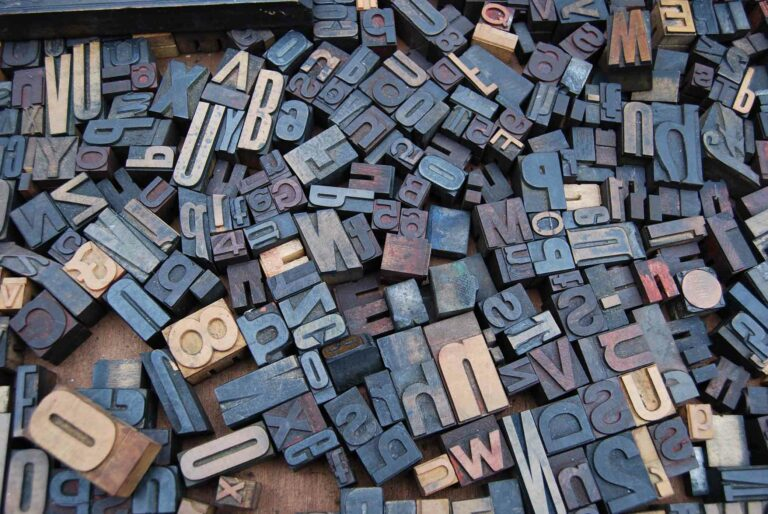 Wooden blocks with letters and numbers all laying in a jumble on the floor.